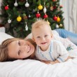Portrait of happy mother and baby boy on bed at home with decorated Christmas tree in background — Stock Photo #59126605