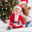 Happy mother putting Santa costume on toddler son at home — Stock Photo #59126649