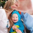 Young parents cover camera with hand while kissing, baby son dressed in little monster costume laughing, Christmas time. — Stock Photo #59126655