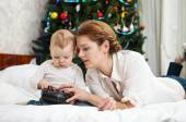 Young Caucasian mother and toddler son playing with RC controller against decorated Christmas tree at home — Stock Photo