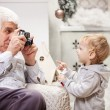 Senior man taking photo of his toddler grandson at Christmas time — Stock Photo #60159927
