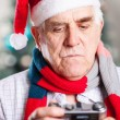 Senior man in Santa's hat looking at display of retro style camera on Christmas background — Stock Photo #60159961