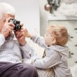 Senior man taking photo of his toddler grandson at Christmas time — Stock Photo #60160107