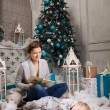 Young woman reading book to toddler son beside Christmas tree, boy falling asleep — Foto Stock #60160141