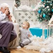 Senior man taking photo of his toddler grandson while sitting near Christmas tree at home — Stock Photo #60160279