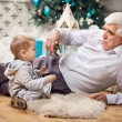 Toddler boy and his grandpa playing with toy dinosaur at Christmas — Stock Photo #60160417