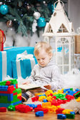Cute toddler boy sitting at Christmas tree and reading book — Foto Stock