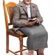 Senior woman using mobile phone while sitting on chair — Stock Photo #62838247
