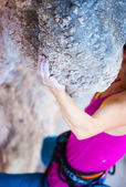 Cropped view of young woman climbing natural cliff, hand in focus — Stock Photo