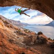 Male rock climber climbing along a roof in a cave at sunset — Stock Photo #63437915