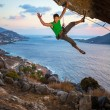 Cheerful rock climber waving his hand while climbing at sunset — Stock Photo #63437925