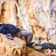 Young man lying on stone and watching leading rock climber while belaying — Stock Photo #63437943