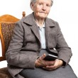 Senior woman sitting on chair and holding mobile phone — Stock Photo #63437983