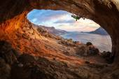 Male rock climber climbing along a roof in a cave at sunset — Stock Photo