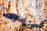 Young man lying on stone and watching leading rock climber while belaying — Stock Photo