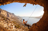 Male rock climber climbing on a roof in a cave, his partner belaying — Stock Photo