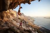 Young woman lead climbing on overhanging cliff — Stock Photo
