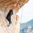 Young man clipping rope while clinging to cliff — Stock Photo #69564839