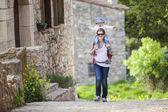 Caucasian woman tourist carrying her little son — Stock Photo