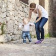 Baby makes his first steps with help of his mother — Stock Photo #69664291