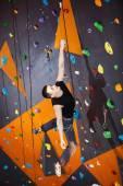 Young man practicing rock-climbing in climbing gym — ストック写真