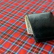 Black purse with money on plaid background — Stock Photo #75532365