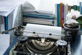Vintage typewriter on a table with books — Stock Photo