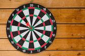 Красный Дарт, торчащий в цель, попасть в цель на деревянной задней — Стоковое фото