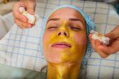 Beautiful woman with facial golden mask at beauty salon. — Foto de Stock