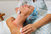 Young and relaxed woman getting a face massage with cream. — Foto de Stock