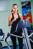 Young woman runs on a treadmill, is engaged in fitness sport club — Stockfoto