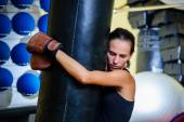Beautiful sporty woman boxing with red punching bag at gym. — 图库照片