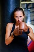 ボクシングのジムで黒いサンドバッグとスポーティな美人. — ストック写真