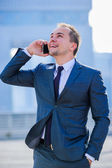 Portrait of yang businessman in suit outdoors. — Stockfoto