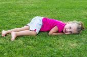 Small cute European girl posing lying down in the green grass. — Stock Photo