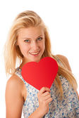Beautiful young blonde woman with blue eyes holding red hart ban — Stock Photo