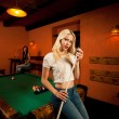 Beautiful young blonde woman playing billiard in a bar — Stock Photo #53197099