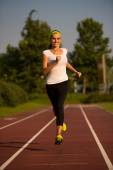 Preety young woman running on a track — Stock Photo