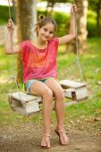 Young girl swinging outdoor in park — Stock Photo