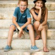 Teenage boy and girl sitting on stairs in park — Stock Photo #55776885