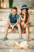Teenage boy and girl sitting on stairs in park  — Stock Photo