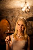 Beautiful young blond woman tasting red wine in a wine cellar — Stock Photo
