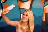 Beautiful young woman making a selfie outdoors near graffiti wal — Photo