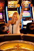 Young blond woman playing roulette in casino and winning — Stock Photo