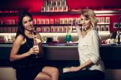 Two beautiful women drinking cocktail in a night club and having — Stock Photo