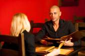 Young couple ordeting food in restaurant reading menu — Stock Photo