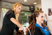 Young woman in hairdresser saloon having a treatment and haircut — Stock Photo