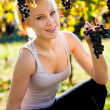 Beautiful young blonde woamn harvesting grapes in vineyard — Stock Photo #62595073