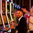 Four young people playing slot machines in casino — Stock Photo #62595731