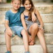 Teenage boy and girl sitting on stairs in park — Stock Photo #63624717